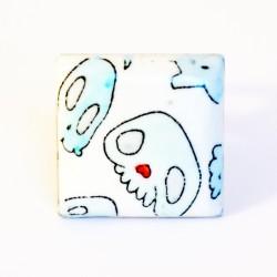 Bague carrée avec des têtes de mort bleues