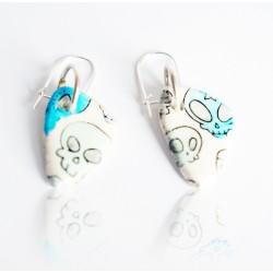 Boucles d'oreilles blanches avec des têtes de mort bleues