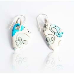 White earrings with blue skulls